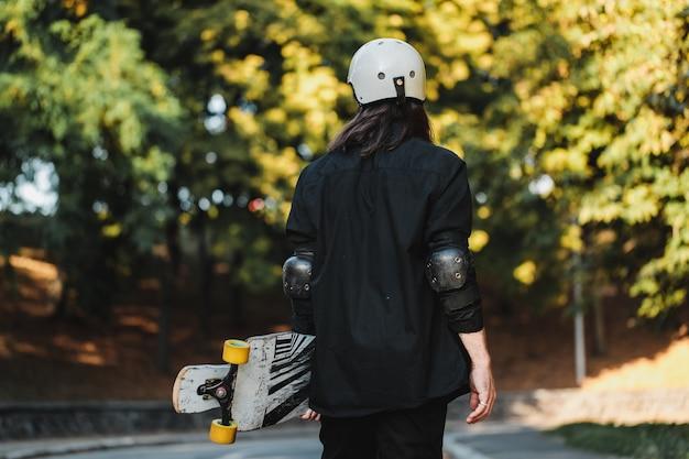 ボードを持った男が通りを歩きます。日没時のロングボーディング。高品質の写真