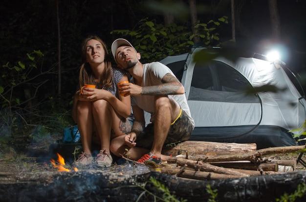 Парень с девушкой в лесу с палаткой ночью сидят у костра
