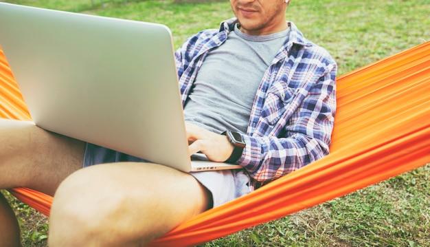 裏庭のハンモックに横たわってオンラインでラップトップを操作している男