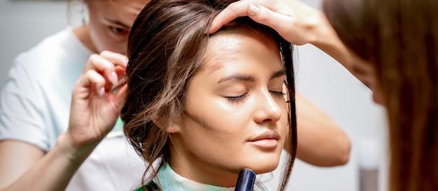 Парикмахер и визажист делают прическу и макияж для красивой молодой кавказской женщины в салоне красоты
