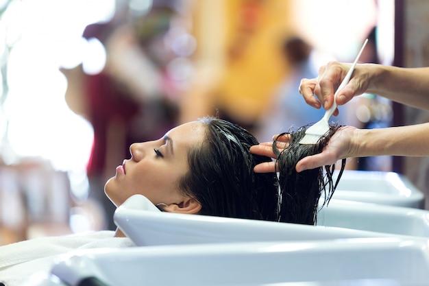 Парикмахер, применяющий лечение волос для клиента в салоне красоты.