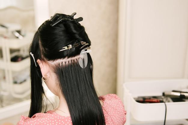 미용사는 미용실에서 어린 소녀에게 헤어 익스텐션을합니다. 전문 헤어 케어. 캡슐과 자란 머리카락의 클로즈업