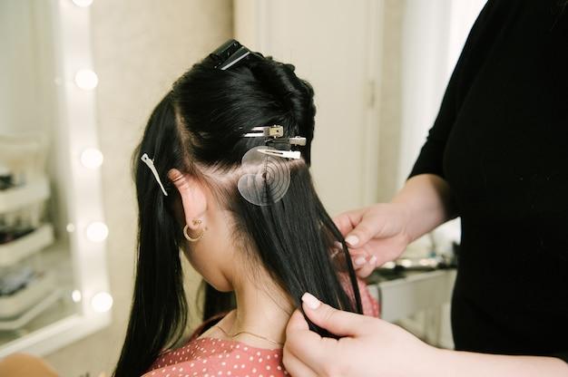 미용사는 미용실에서 어린 소녀의 머리카락을 확장합니다. 전문 헤어 케어.