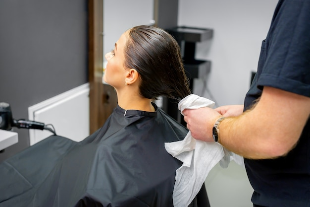 미용사는 뷰티 살롱에서 아름다운 젊은 갈색 머리 여자에게 수건으로 씻은 머리카락을 말립니다.