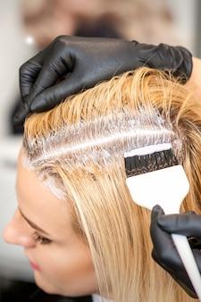 Парикмахер окрашивает корни светлых волос щеткой для молодой женщины в парикмахерской