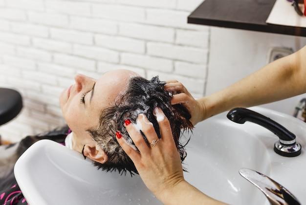 美容師の女の子が美容院でクライアントの髪を優しく洗います。