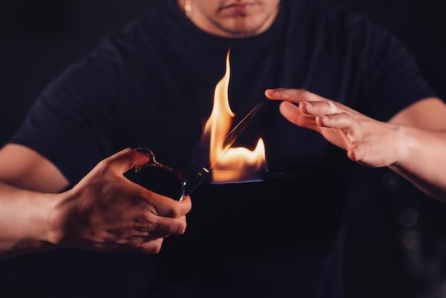 Парикмахер держит в руках ножницы, на которых пламя