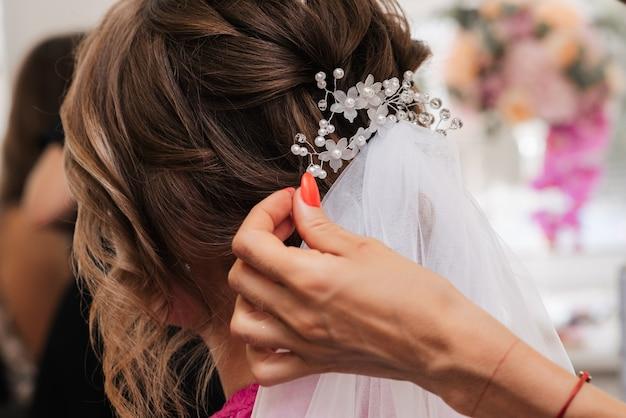 Элегантную прическу для укладки невесты с белыми украшениями в волосах парикмахер делает в салоне красоты.