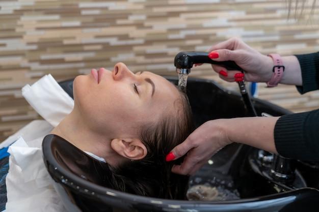 Парикмахер ополаскивает волосы девушке перед стрижкой.