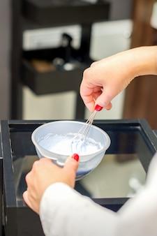 헤어 스타일리스트는 살롱 클로즈업에서 머리카락을 염색하기 위해 흰색 염료 믹스를 만듭니다.