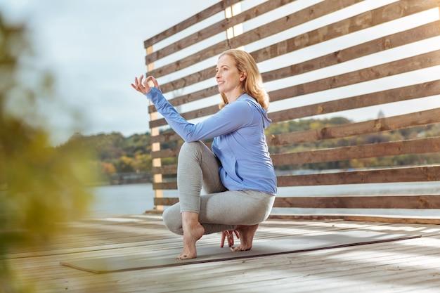 Поза полувластителя рыб. женщина, практикующая асаны йоги утром