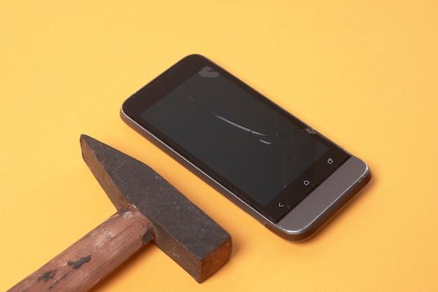 ハンマーは壊れた電話の隣にあります