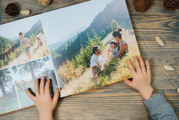 Рука ребенка, держащая семейный фотоальбом деревянного стола