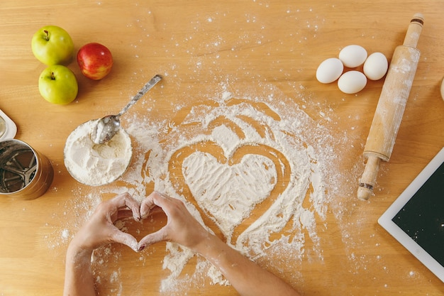 Рука нарисованные сердце в муке на кухонном столе и других ингредиентах и таблетке. вид сверху.