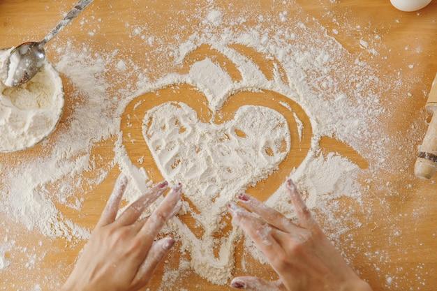 Сердце нарисованное рукой в муке на кухонном столе и других ингредиентах. вид сверху.
