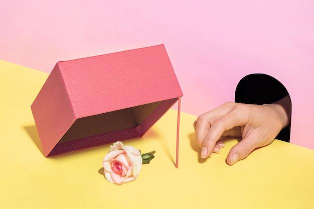穴からの手は、罠からバラの花を盗もうとしています。パステルシュールなコンセプト。