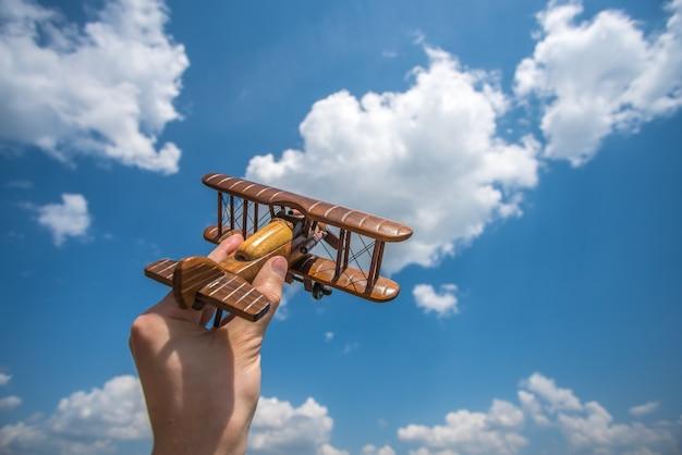 手は雲の背景におもちゃの飛行機を持っています