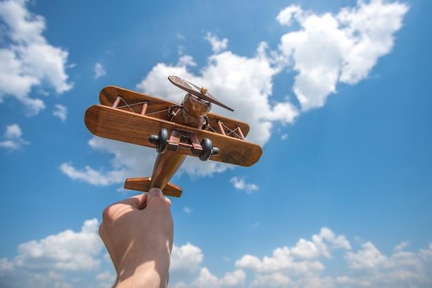手は雲の背景に木製の飛行機を持っています