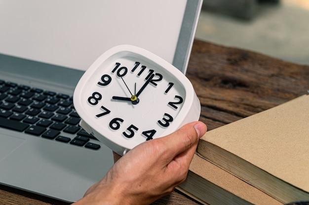 시계를 들고있는 손이 책상에 있습니다.