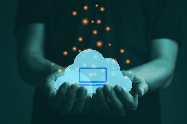 Рука, держащая облако со значком ноутбука, облачный центр обработки данных и сервис, новые технологии для делового соединения с компьютерным графическим светом