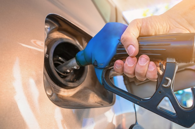 車に燃料を補給する銃のガソリンスタンドを持っている手