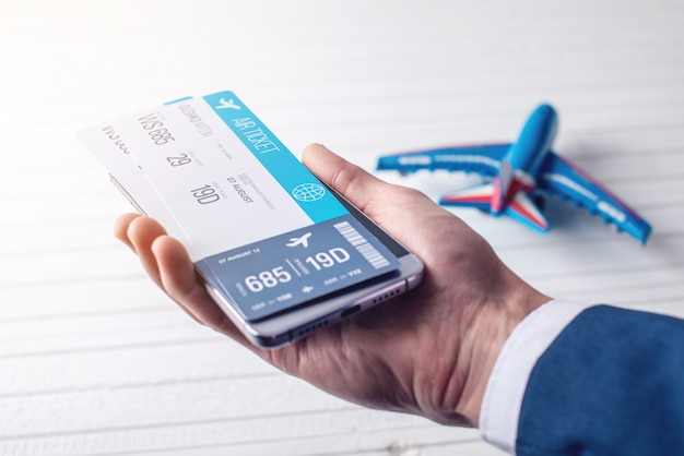 Рука держит телефон с билетами на самолет