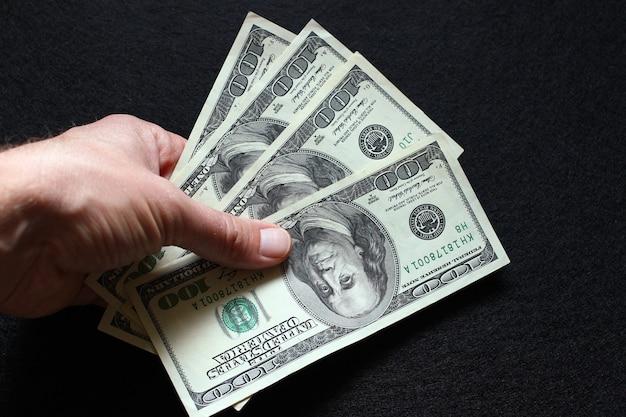 Рука держит 100 долларов крупным планом