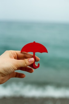 手は海のシンボルの背景にミニチュアの赤い傘を持っています。