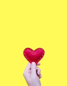 手は黄色の背景に白い糸で布で作られた赤いハートを持っています。愛、恋愛の概念。刺し繡のラインで明るい心を感じました。