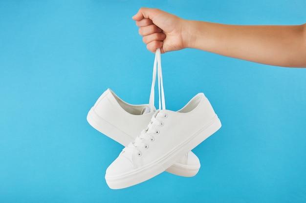 Рука держит шнурками пара модных стильных белых кроссовок на пастельно-синем фоне.
