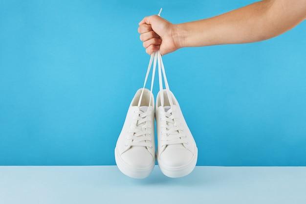 신발 끈에 의해 손 보유 파스텔 파란색 배경에 패션 세련 된 흰색 스 니 커 즈의 쌍.