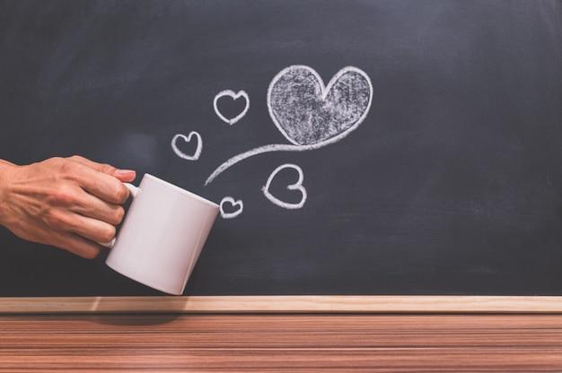 손은 커피 컵을 잡고 심장 모양은 칠판에 있습니다.