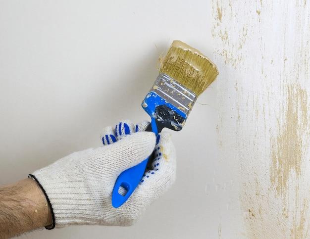 Рука в перчатке наносит декоративную краску на стену.