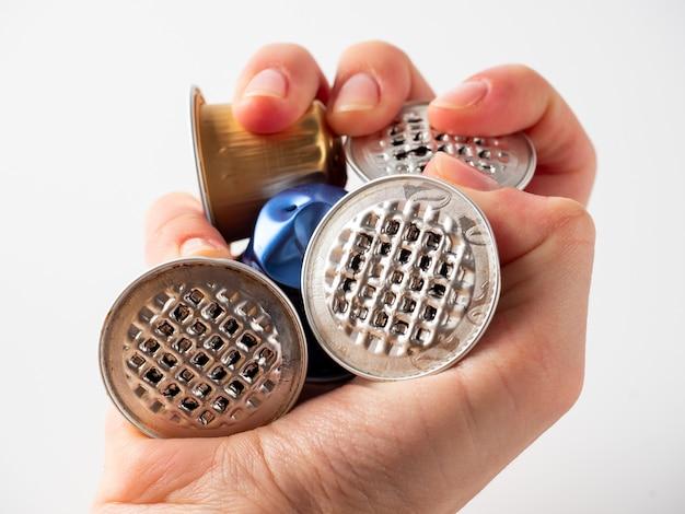 手は使用済みのアルミカプセルをたくさん握っています。製品の再利用の概念。