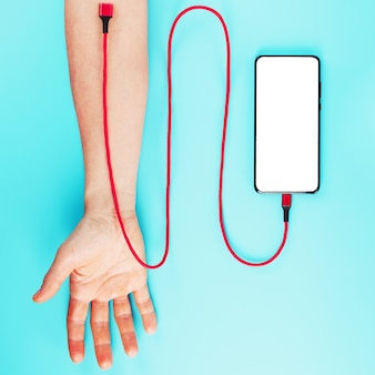 손은 빨간색 전원 코드로 파란색 표면의 스마트 폰에 연결됩니다.