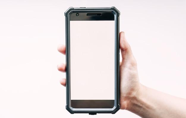 手は白いディスプレイのスマートフォンデバイスを持っています
