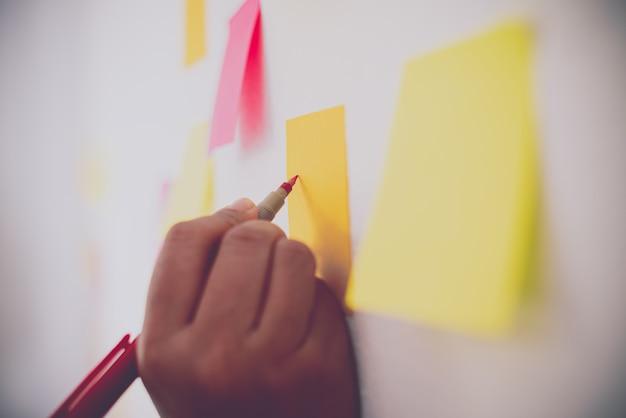 손은 벽에 붙은 노트를 잡고있다. 개념 브레인 스토밍, 아이디어 공유.