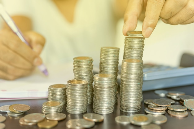 Рука кладет монеты, и монеты накапливаются в столбце, который представляет экономию денег или идею финансового планирования для экономики.
