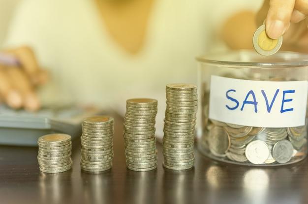 Рука кладет монеты в бутылку и накапливает их в столбце, который представляет экономию денег или идею финансового планирования для экономики.