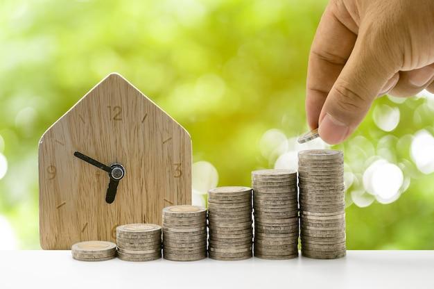 Рука кладет монеты в столбец с домом на заднем плане, который представляет идею экономии денег или финансового планирования для экономики.