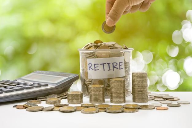 Рука кладет монеты в пенсионную бутылку и накапливает их в столбце, который представляет экономию денег или идею финансового планирования для экономики.