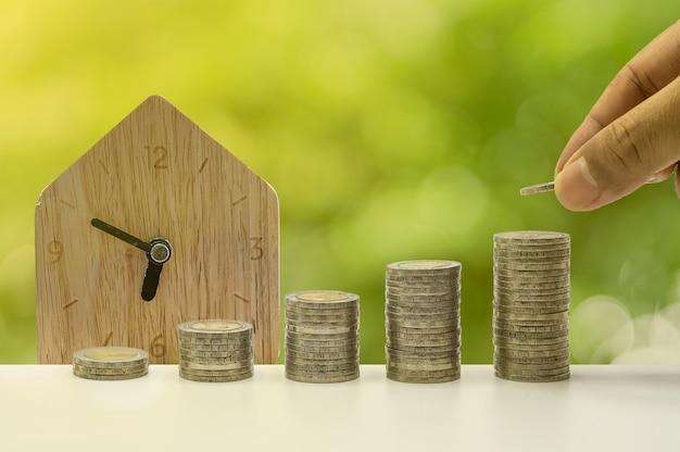 Рука кладет монеты на столбец с домашними часами на заднем плане, которые представляют идею экономии денег или финансового планирования для экономики.