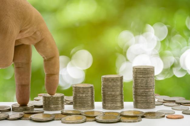 Рука наступает на монеты, уложенные стопкой, и монеты накапливаются в столбце, который представляет экономию денег или идею финансового планирования для экономики.