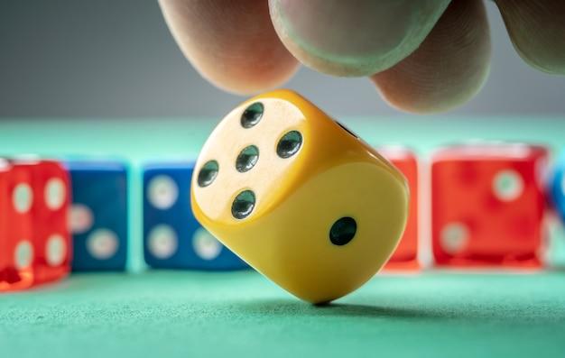 손이 녹색 테이블에 노란색 주사위를 던지고 있습니다. 카지노의 개념과 이길 수 있는 행운의 기회