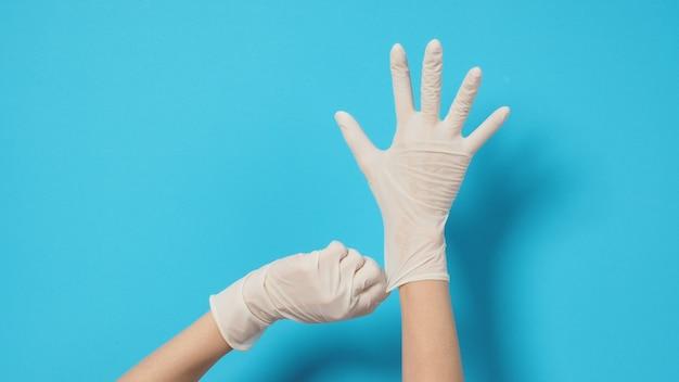 손은 파란색 또는 청록색 배경에 흰색 수술용 장갑이나 라텍스 장갑을 끼고 있습니다.