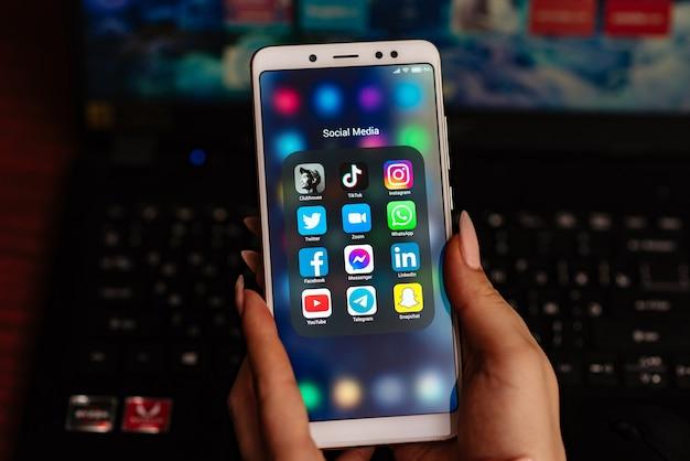 손이 클럽 하우스 앱과 화면의 다른 소셜 미디어와 함께 스마트 폰 화면을 가로 질러 움직입니다.