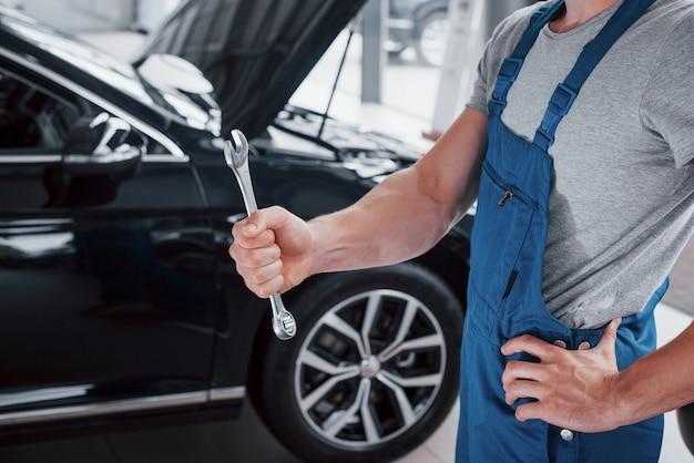 Рука автомеханика с гаечным ключом в зоне комби возле машины в мастерской.