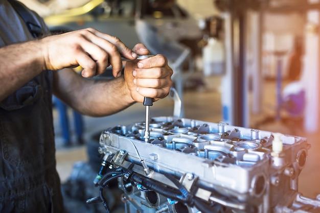 Рука мастера по ремонту автомобилей со специальным инструментом на фоне зоны обслуживания.