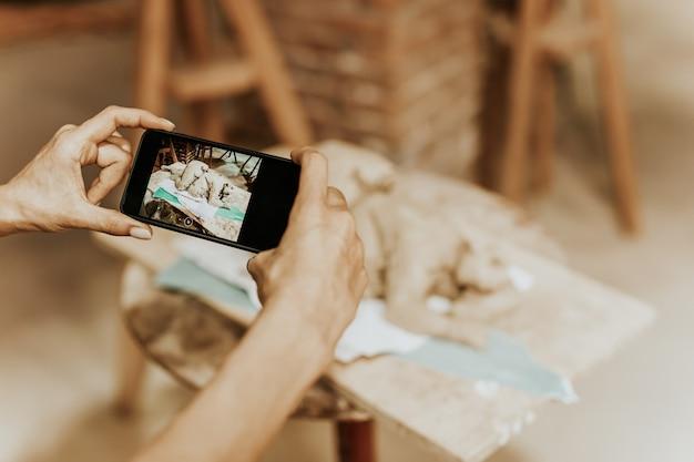 女性彫刻家の手が携帯電話を持って、彼女のアートワークを写真に撮ります。クローズアップショット。