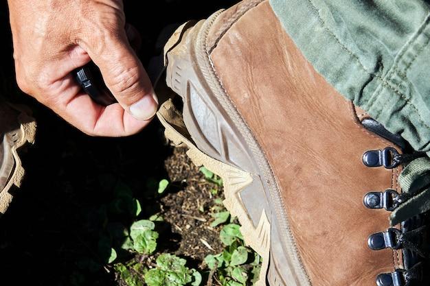 격렬한 걷기로 벗겨진 등산화의 밑창을 보여주는 등산객의 손